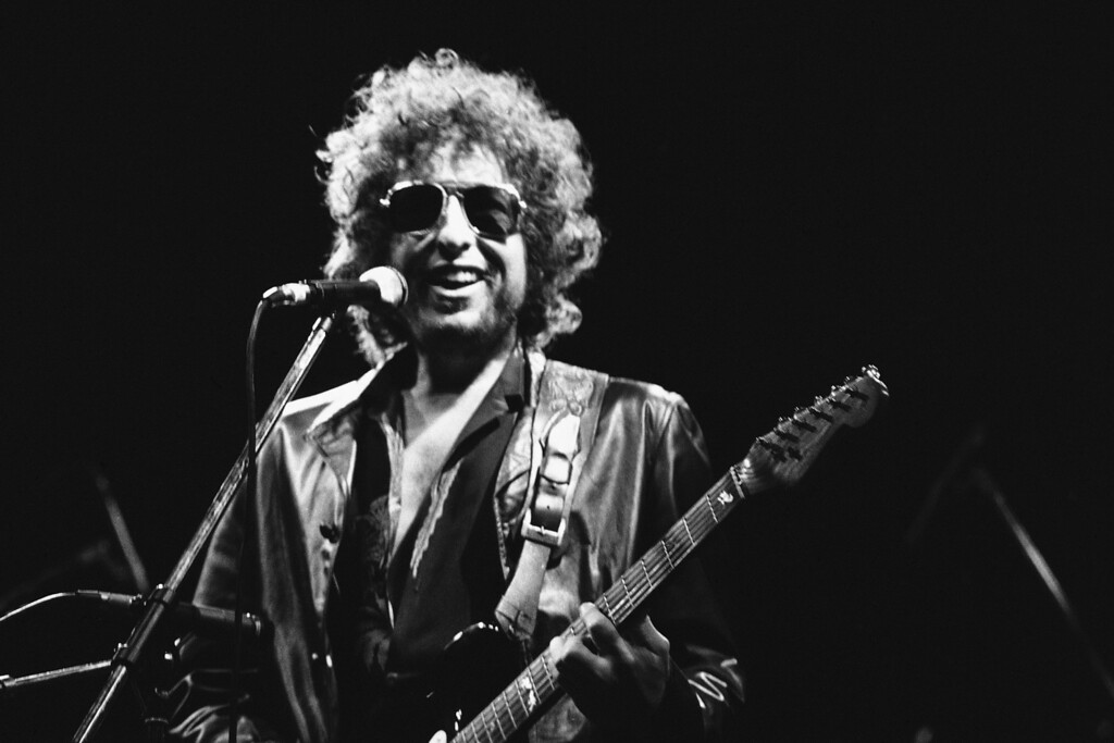 . American singer Bob Dylan smiles as he performs during his show on Tuesday, June 24, 1981 at the Colombes Olympic stadium, West of Paris, France in front of an estimated crowd of 40,000 fans. (AP Photo/Herve Merliac)