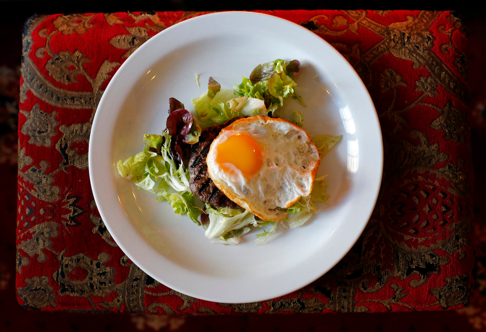 ". A ""Steak de Cheval\"", a 100% horsemeat burger, served with a fried egg on a bed of lettuce is displayed at Chez Sophie, a French restaurant at Knockholt, southern England on February 15, 2013. The horsemeat burgers are sold legally and listed on the menu. Some supermarkets in Britain have recently been hit by a scandal involving the mislabeling of beef products.     REUTERS/Andrew Winning"