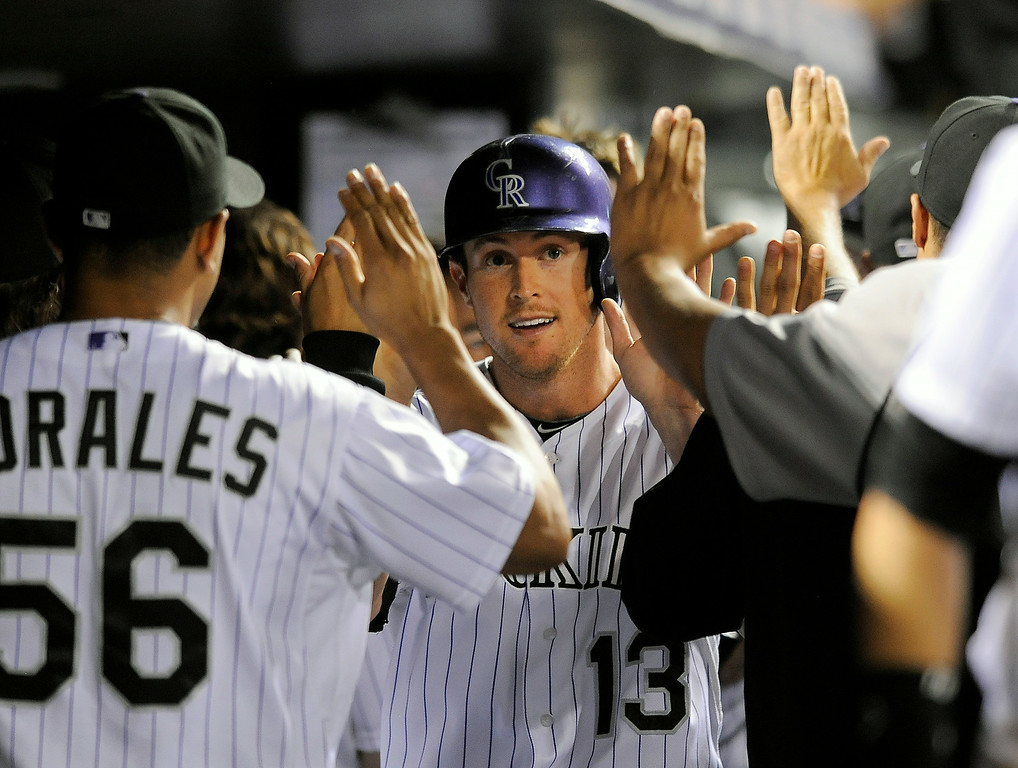 . Colorado Rockies Drew Stubbs is congratulated by teammates after scoring on a three-run double by Josh Rutledge in the seventh inning of a baseball game against the Pittsburgh Pirates on Friday, July 25, 2014, in Denver. (AP Photo/Chris Schneider)