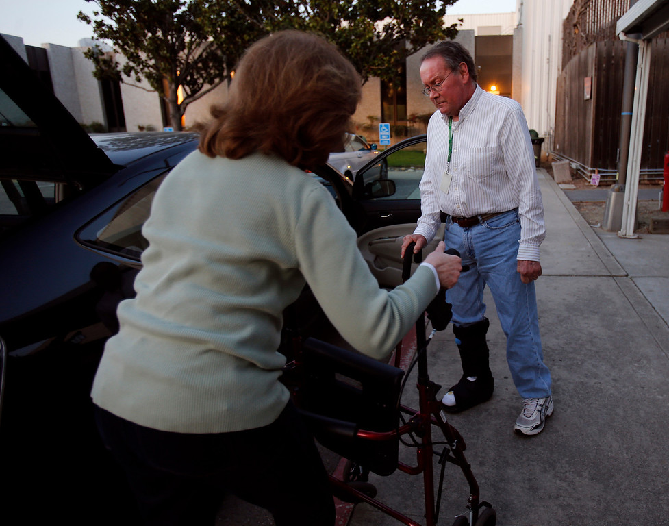 . Jan Richards , left, grabs her husband Gary, also known as Mr. Roadshow, walker while he enters their Toyota Prius for their drive home from the San Jose Mercury News office in San Jose, Calif., on March 4, 2013.  Richards is writing a column about how he cannot drive for six to eight months while his right foot heals. The theme is how this affects the Merc\'s Mr. Roadshow columnist and now is an issue that many older motorists will be facing as our population ages and driving skills diminish.  His wife Jan must now drive him everywhere he needs to go, including to and from work until his foot heals.  (Nhat V. Meyer/Staff)