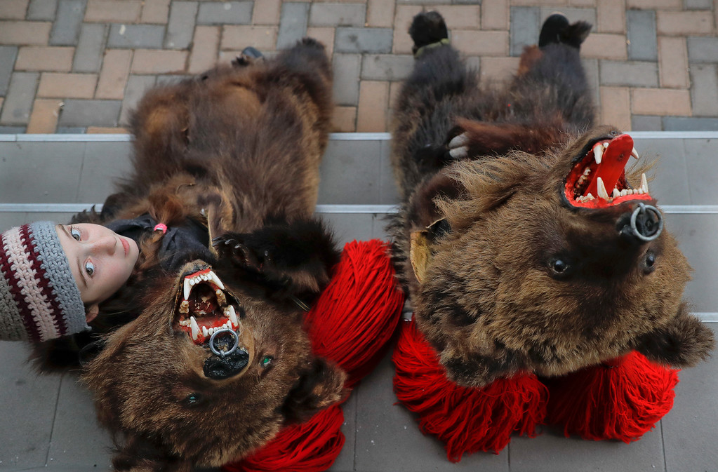 . In this Saturday, Dec. 30, 2017, picture, Cleopatra Antonia Turcu, 10 years-old, wearing a bear fur costume pauses next to Georgiana Andresoaie, during an annual bear parade in Comanesti, Romania. The tradition, originating in pre-Christian times, when dancers, wearing colored costumes or animal furs, went from house to house in villages singing and dancing to ward off evil, has moved to Romania\'s cities, where the ritual is performed for money.(AP Photo/Vadim Ghirda)