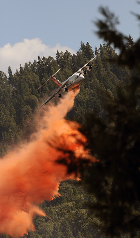 . A jet aerial tanker drops its load of fire retardant on a fire near Pollack Pines, Calif., Monday, Sept. 15, 2014. The fire, which started Sunday has consumed more than 3,000 acres and forced the evacuation of dozens of homes.(AP Photo/Rich Pedroncelli)