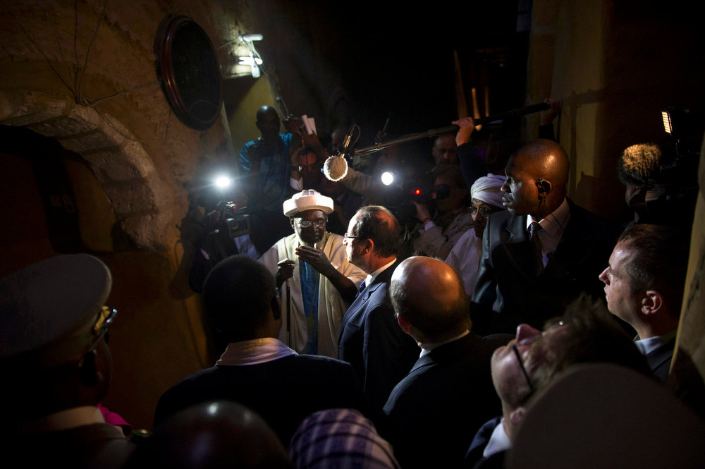 Description of . France\'s President Francois Hollande (C) flanked by Mali\'s interim president Dioncounda Traore (2ndL), visit the Djingareyber Mosque in Timbuktu during his one-day visit in Mali,  February 2, 2013. President Hollande flew to Mali on Saturday to support French troops fighting Islamist rebels in the Sahel nation and he visited the famed ancient city of Timbuktu that was recaptured from al Qaeda-allied fighters six days ago. REUTERS/Fred Dufour/Pool