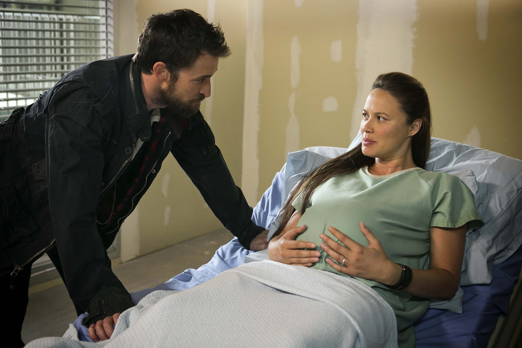 . Tom (Noah Wyle) checks on Dr. Anne Glass (Moon Bloodgood) as she prepares for the delivery of their baby.  Photo Credit: James Dittiger