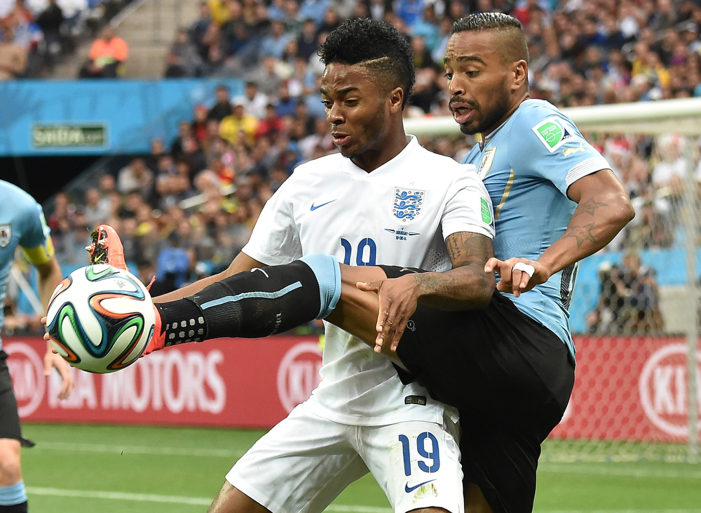 . England\'s midfielder Raheem Sterling (L) vies for the ball with Uruguay\'s midfielder Alvaro Pereira (R) during a Group D football match between Uruguay and England at the Corinthians Arena in Sao Paulo during the 2014 FIFA World Cup on June 19, 2014. (LUIS ACOSTA/AFP/Getty Images)