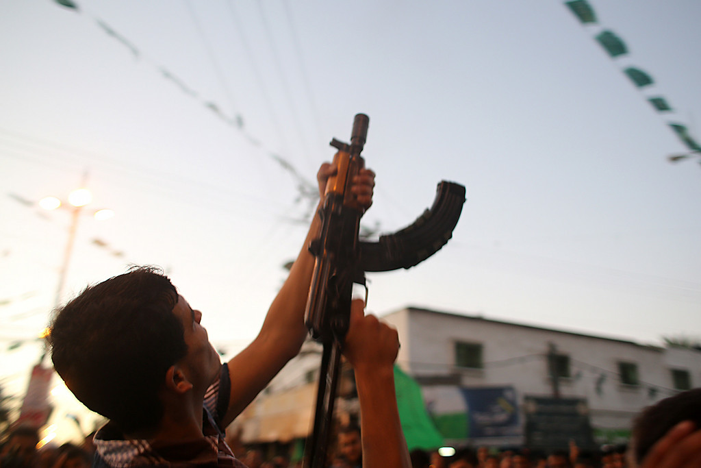 """. A Palestinian fires rounds into the air as people gather in the streets to celebrate after a deal had been reached between Hamas and Israel over a long-term end to seven weeks of fighting in the Gaza Strip on August 26, 2014 in Rafah in the southern of Gaza Strip. Israel has agreed to observe an \""""unlimited\"""" ceasefire in the Gaza Strip, a senior official told AFP, shortly after the deal was announced by the Palestinians. SAID KHATIB/AFP/Getty Images"""