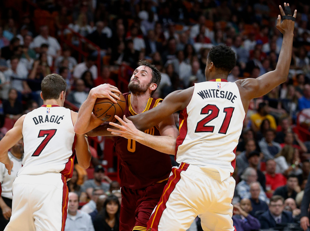 . Cleveland Cavaliers forward Kevin Love (0) attempts a shot against Miami Heat center Hassan Whiteside (21) and guard Goran Dragic (7) during the first half of an NBA basketball game, Monday, April 10, 2017, in Miami. (AP Photo/Wilfredo Lee)