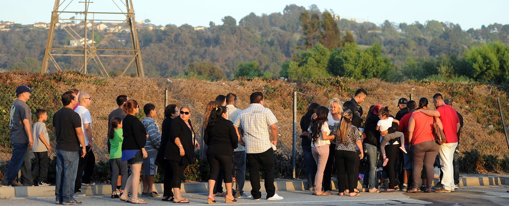 . Over 40 family and friends stand in front of a make shift memorial during a vigil for those who died in a car crash including  two children and a man along the 3500 block of San Gabriel River Road on Friday, June 14, 2013 in Industry, Calif.  (Keith Birmingham/Pasadena Star-News)