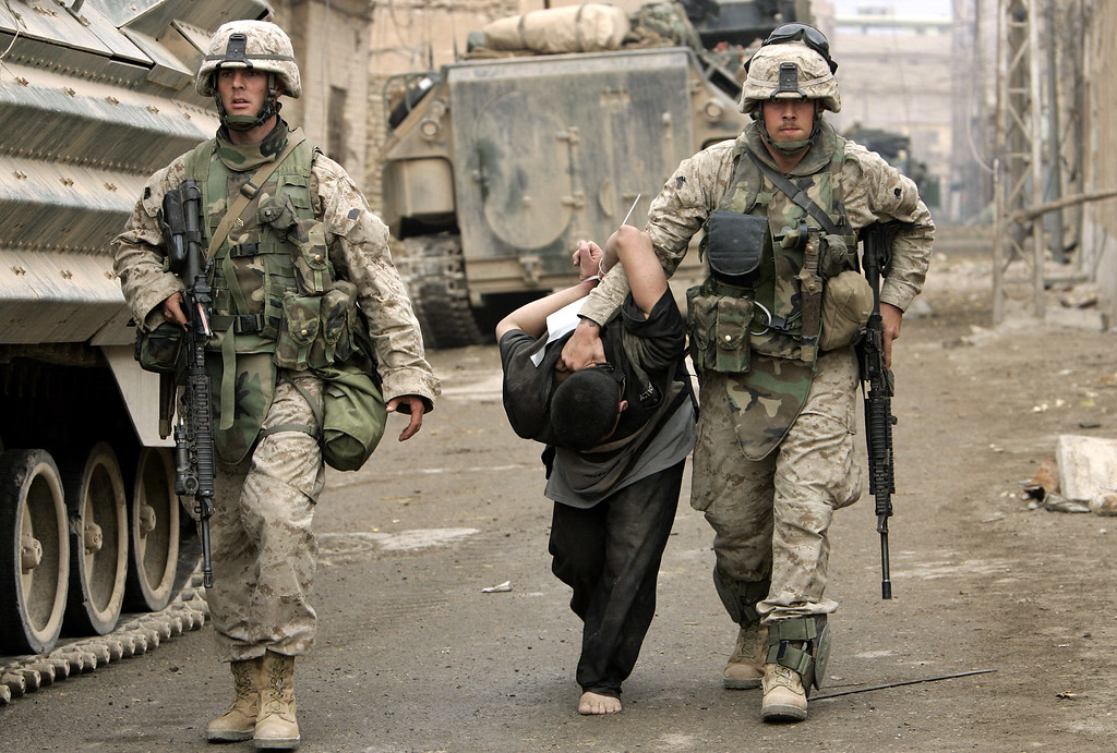 . US Marines lead away  a captured Iraqi man in the center of Fallujah, Iraq, Friday, Nov. 12, 2004.  Trooping past dead bodies and abandoned weapons, U.S. Marines fighting their way through Iraq\'s rebel-infested Fallujah are blasting their way through walls and hammering open doors seeking fighters and guns in the dayslong battle against Sunni Muslim insurgents.   (AP Photo/Anja Niedringhaus)