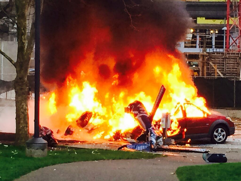. In this photo provided by KOMO-TV, a car burns at the scene of a helicopter crash outside the KOMO-TV studios near the space needle in Seattle on Tuesday, March 18, 2014.  (AP Photo/KOMO-TV, Kelly Koopmans)