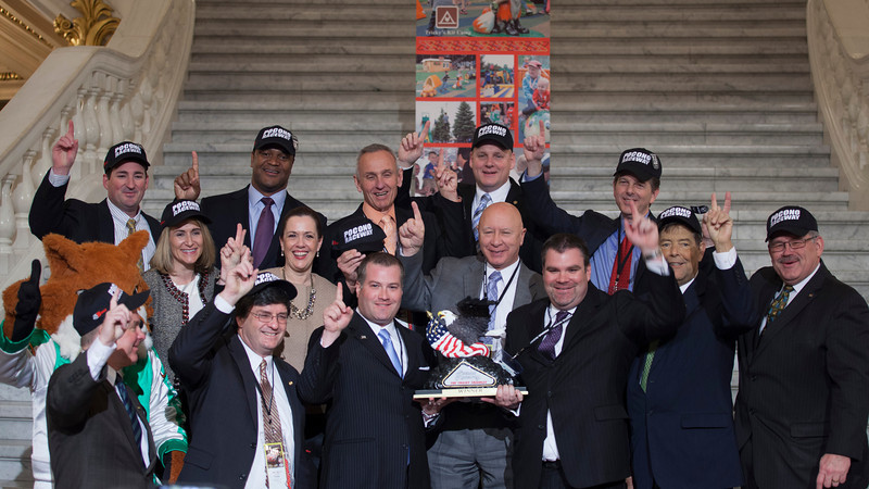 """PA Capitol Rotunda was turned into Victory Lane on March 10, 2014.  Standing Left to Right - Rep. Mike Peifer; Pocono Raceway Mascot, """"Tricky""""; Sen. David Argall; Rep. Rosemary Brown; Marcus Jadotte, VP Public Affairs NASCAR; Rep. Mike Carroll, Sen. Lisa Baker; Nick Igdalsky, Executive Vice President & COO of Pocono Raceway; Rep. Sid Kavulich; Rep. Mario Scavello; Rep. Doyle Heffley; Brandon Igdalsky, President & CEO of Pocono Raceway C.J. O'Donnell, Chief Marketing Officer, Hulman Sports; Rep. Jerry Stern; and Sen. Tim Sollobay"""