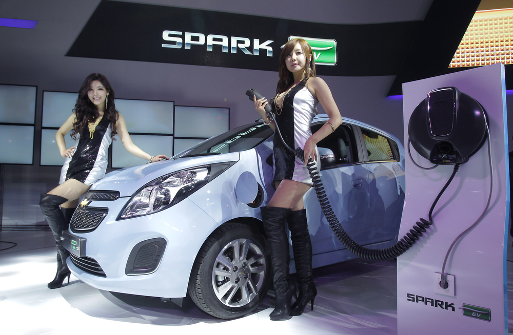. Models pose next to a Chevrolet Spark EV at the Seoul Motor Show 2013 on March 28, 2013 in Goyang, South Korea. The Seoul Motor Show 2013 will be held in March 29-April 7, featuring state-of-the-art technologies and concept cars from global automakers. The show is its ninth since the first one was held in 1995. About 384 companies from 14 countries, including auto parts manufacturers and tire makers, will set up booths to showcase trends in their respective industries, and to promote their latest products during the show.  (Photo by Chung Sung-Jun/Getty Images)