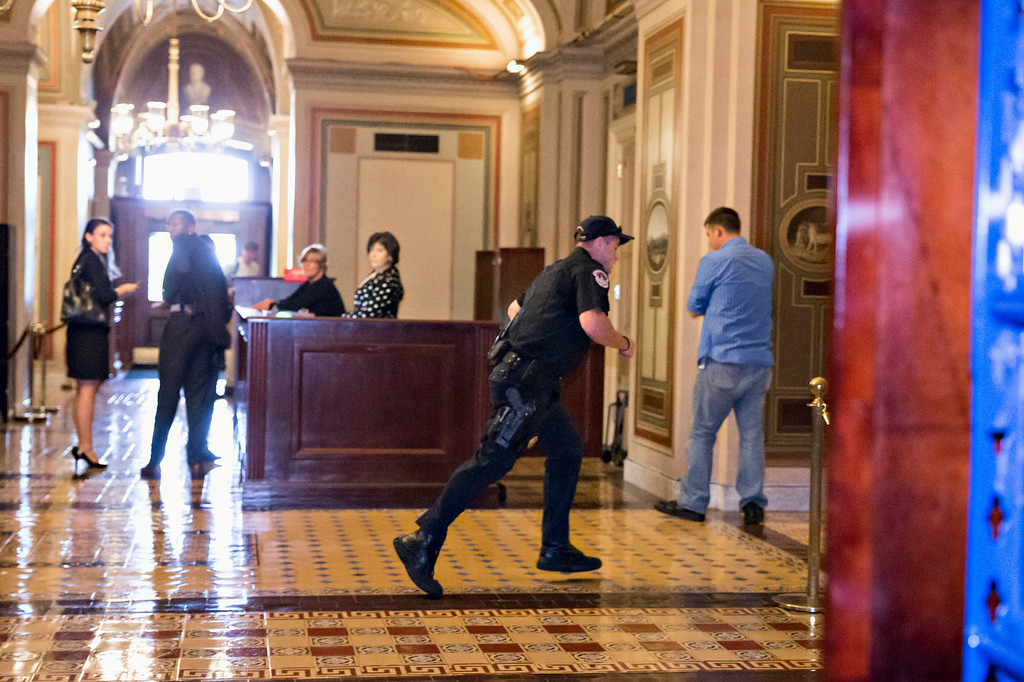 . A Capitol Police officer runs through the first floor of the Senate on Capitol Hill in Washington, Thursday, Oct. 3,2013, during the lockdown order following a shooting on Constitution Avenue on Capitol Hll and near the Supreme Court. A police officer was reported injured after gunshots at the U.S. Capitol, police said Thursday. They locked down the entire complex, at least temporarily derailing debate over how to end a government shutdown.   (AP Photo/J. Scott Applewhite)