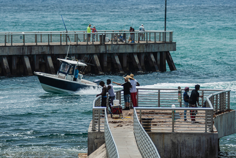 People fish from the north and south jetties as a boat enters the inlet at the Boynton Inlet in Boynton Beach, Sunday, June 28, 2020. [JOSEPH FORZANO/palmbeachpost.com]