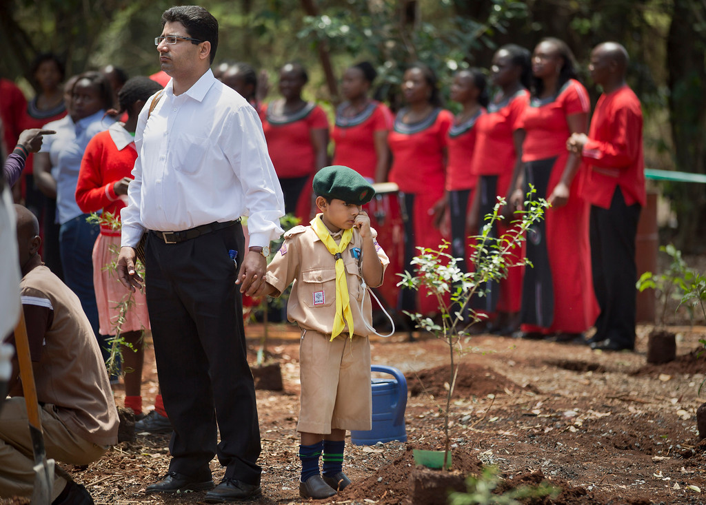 . Khalil Rashid, 6, wears a scouts uniform as he holds the hand of his father and waits to plant a tree in memory of his schoolmate Jennah Bawa, 8, from Britain, who was shot along with her mother Zahira, at a memorial service and tree-planting marking the one-month anniversary of the the Sept. 21 Westgate Mall terrorist attack, in Karura Forest in Nairobi, Kenya Monday, Oct. 21, 2013.  (AP Photo/Ben Curtis)