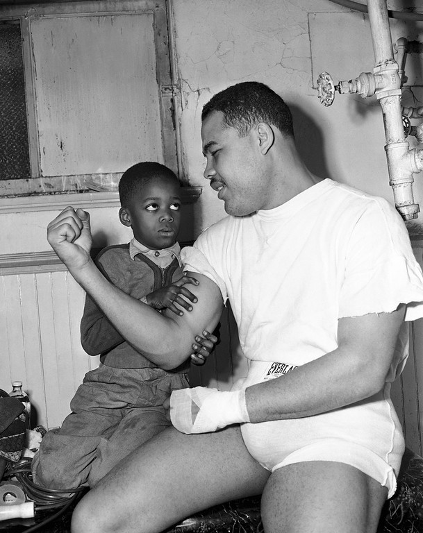 . Heavyweight champion Joe Louis, working out in Chicago on Jan. 23, 1948 at Nichols Gym, lets Robert McElroy, six, feel his right arm muscle, just before Joe entered the ring for a workout for the first time since he defended his title against Jersey Joe Wolcott.    He will fight an exhibition in Chicago on January 29. (AP Photo/ Ed Maloney)