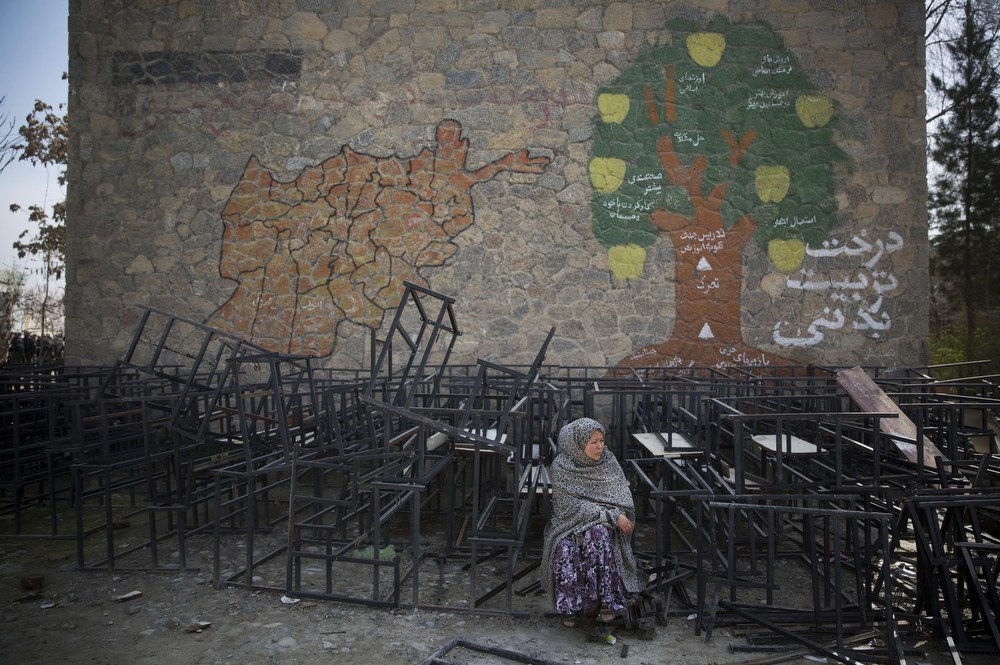 . An Afghan woman sits on destroyed school benches as she waits to get her registration card on the last day of voter registration for the upcoming presidential elections outside a school in Kabul, Afghanistan, Tuesday, April 1, 2014. Elections will take place on April 5, 2014. (AP Photo/Anja Niedringhaus)