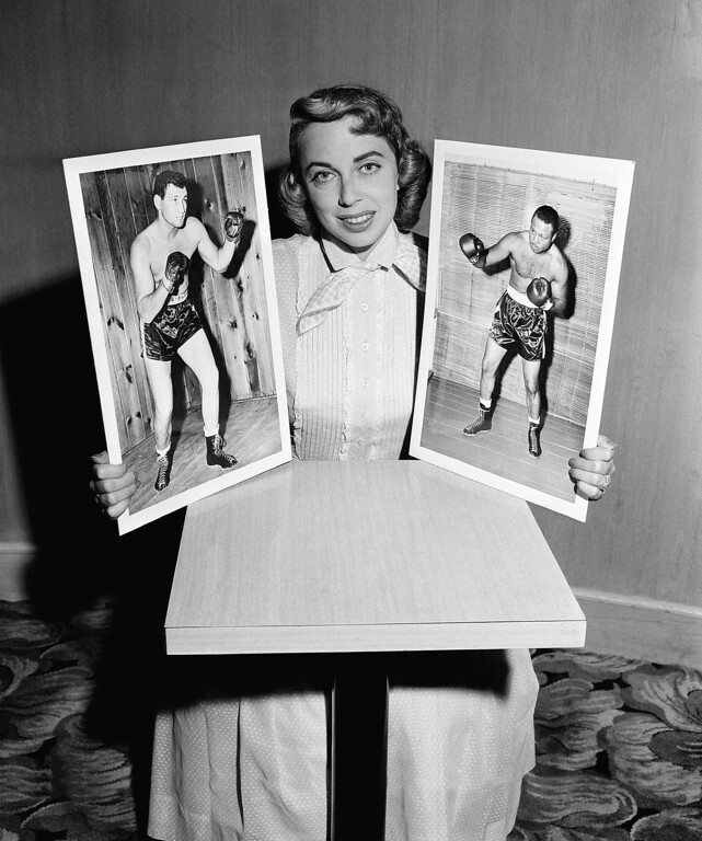. Dr. Joyce Brothers, child psychologist who hit the $64,000 jackpot in quiz on boxing knowledge is shown with photos of boxers James J. Parker, left, and opponent Archie Moore, July 22, 1956. (AP Photo)