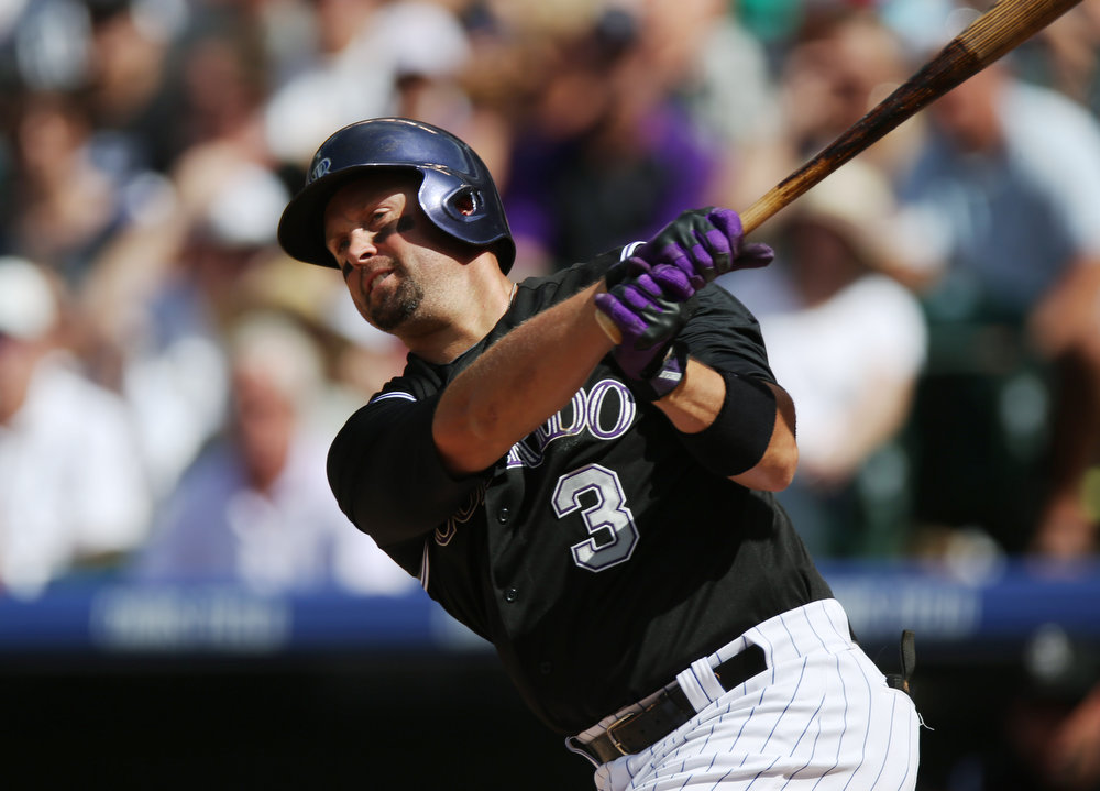 . Colorado Rockies\' Michael Cuddyer swings at a pitch against the Cincinnati Reds in the third inning of a baseball game in Denver, Sunday, Aug. 17, 2014. (AP Photo/David Zalubowski)