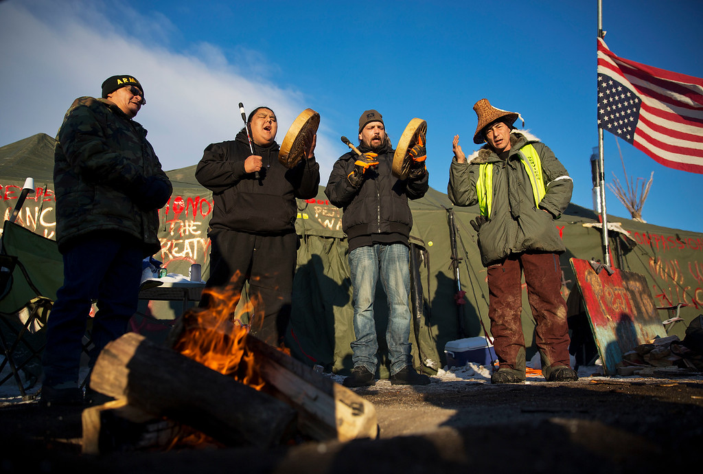 . Native Americans from left, Eugene Sanchez, Jason Umtuch, Martan Mendenhall, and Hugh Ahnatock, all of Portland, Ore., drum and sing at the Oceti Sakowin camp where people have gathered to protest the Dakota Access oil pipeline in Cannon Ball, N.D., Sunday, Dec. 4, 2016. The U.S. Army Corps of Engineers said Sunday that it won\'t grant an easement for the Dakota Access oil pipeline in southern North Dakota, handing a victory to the Standing Rock Sioux tribe and its supporters, who argued the project would threaten the tribe\'s water source and cultural sites. (AP Photo/David Goldman)