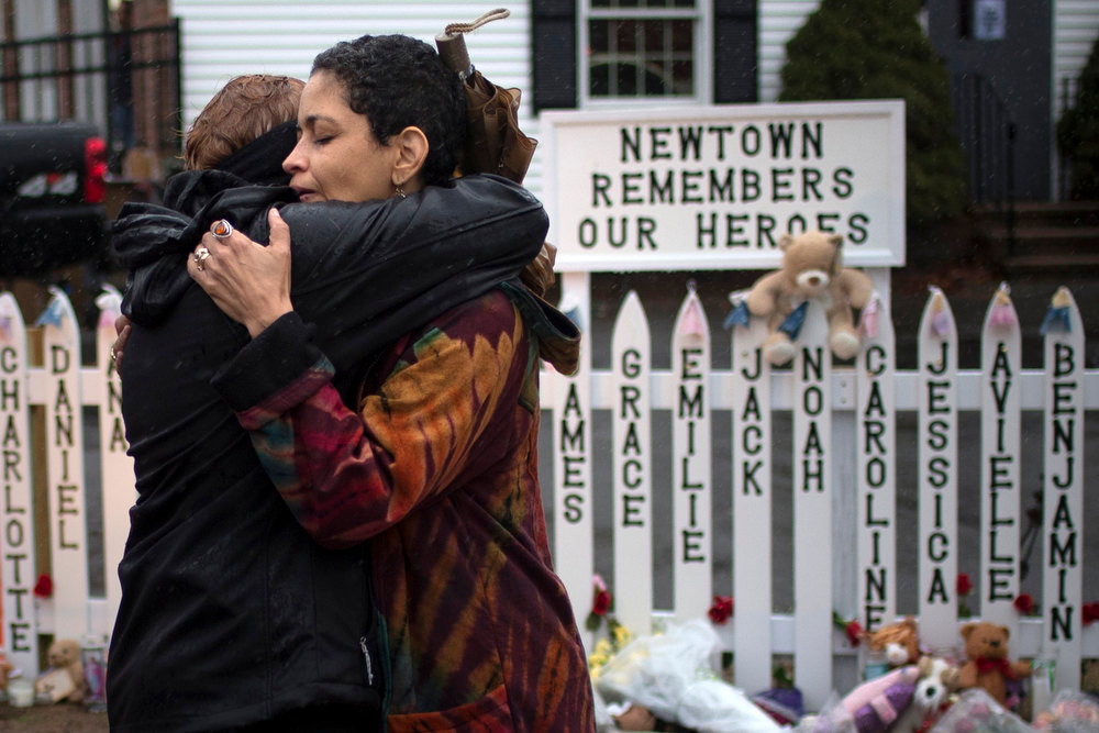 . Women embrace after observing a moment of silence nearby Sandy Hook Elementary in Newtown, Connecticut December 21, 2012. Many Americans remembered the victims of the Newtown, Connecticut, school massacre with a moment of silence on Friday, as a powerful U.S. gun rights lobbying group prepared to plunge into the national debate over gun control.  REUTERS/Adrees Latif