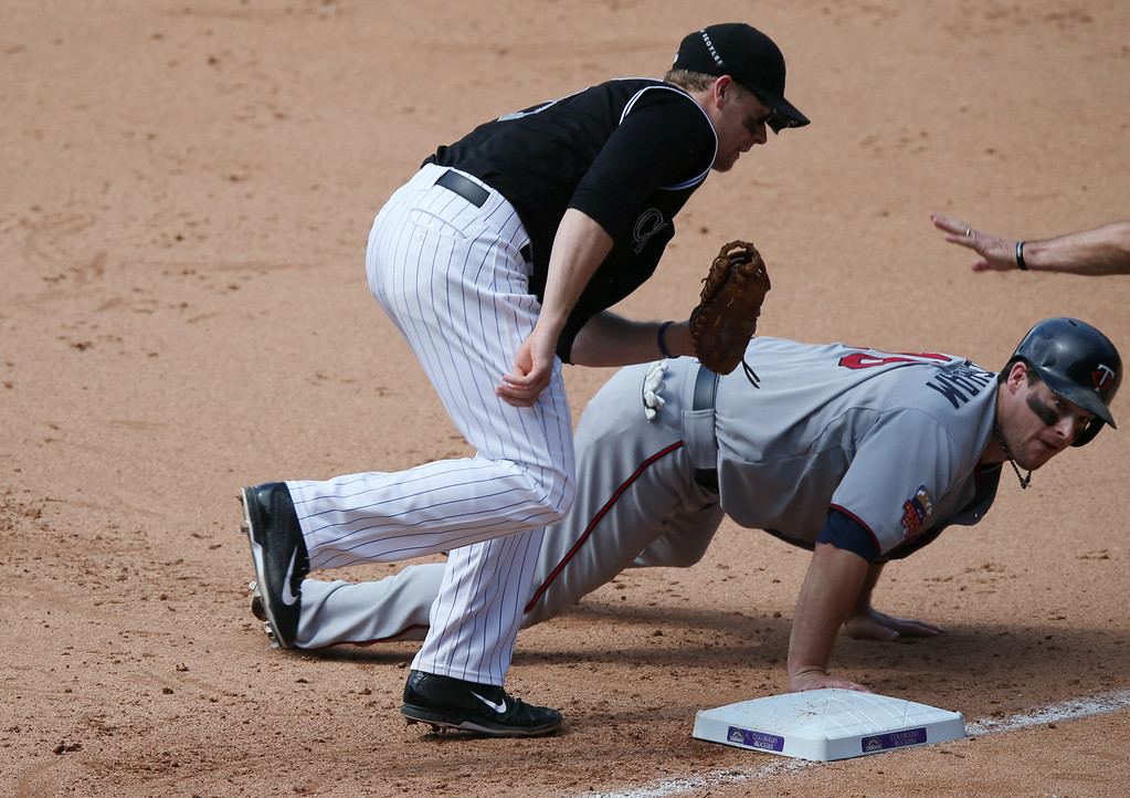 . Colorado Rockies first baseman Justin Morneau, front, turns to tag Minnesota Twins\' Josh Willingham who dives back into first base after a pickoff attempt  in the fifth inning. (AP Photo/David Zalubowski)