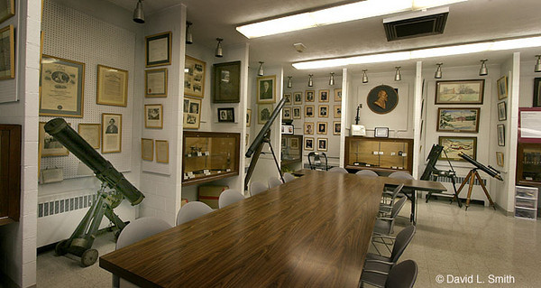 This picture shows quite a number of interesting things. A Brashear reflector can be seen on the far left on wheels. Portraits of John A Brashear abound as well as certificates as to his accomplishments. One of the telescopes in this picture is the very first a young John Brashear first looked into.