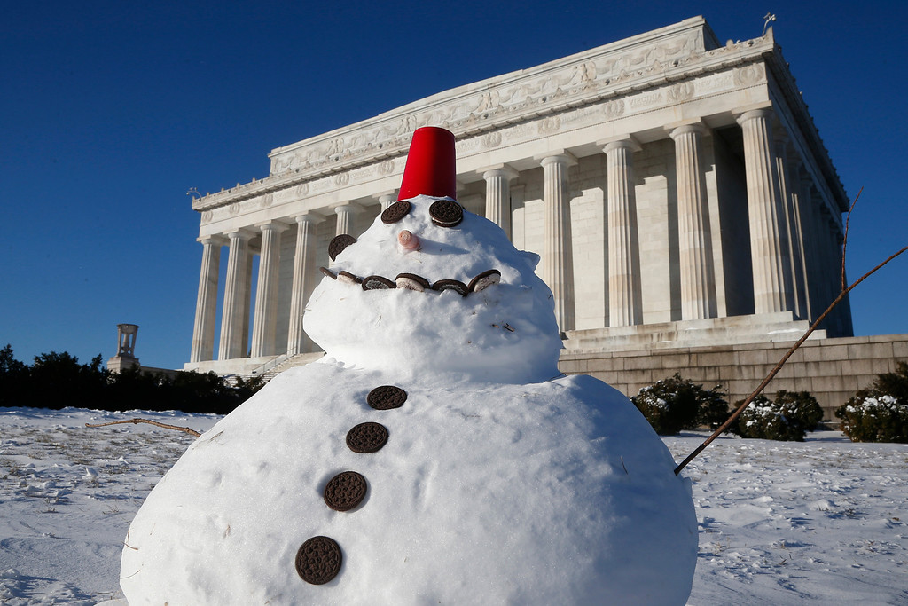 . A snowman made with cookies and a red plastic cup sits in front of the Lincoln Memorial in Washington, Wednesday, Jan. 22, 2014. Snow blowers whirred and shovels scraped across sidewalks on Wednesday as the Northeast started cleaning up from a winter storm that swirled up the coast, creating blizzard conditions on Cape Cod, disrupting government work in Washington and leaving behind bitter cold that sapped fuel supplies. (AP Photo/Charles Dharapak)