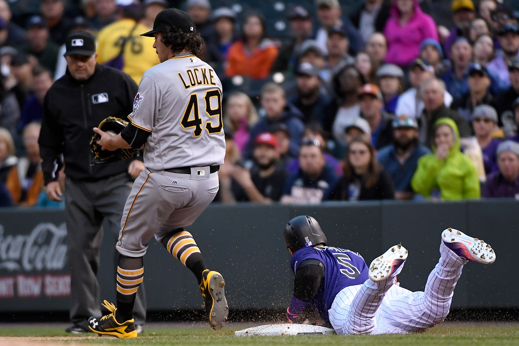 . DENVER, CO - APRIL 25: Carlos Gonzalez (5) of the Colorado Rockies slides head first into first base safely for a single as Jeff Locke (49) of the Pittsburgh Pirates receives the throw during the first inning at Coors Field. The Colorado Rockies hosted the Pittsburgh Pirates on Monday, April 25, 2016. (Photo by AAron Ontiveroz/The Denver Post)