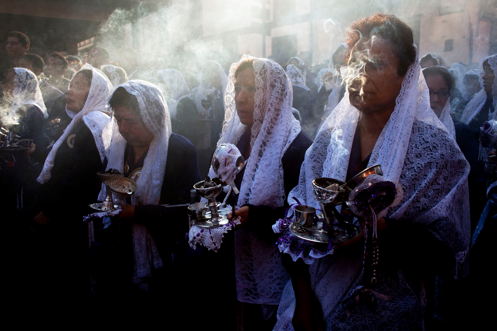 ". Women burn incense while participating in a Good Friday procession honoring ""The Lord of Miracles\"", the patron saint of Lima, Peru, on Friday, April 18, 2014. Christians all over the world are marking Good Friday, the day when Jesus Christ was crucified. (AP Photo/Rodrigo Abd)"