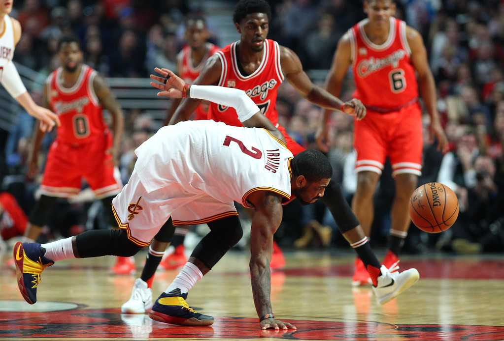 . Cleveland Cavaliers guard Kyrie Irving (2) loses control of the ball while guarded by Chicago Bulls guard Justin Holiday (7) during the second half of an NBA basketball game in Chicago on Saturday, April 9, 2016. (AP Photo/Jeff Haynes)