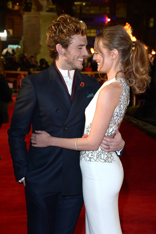 . English actors Sam Claflin and Laura Haddock pose for photographers as they arrive on the red carpet for the World Premiere of \'The Hunger Games: Catching Fire\', in London, Monday Nov. 11, 2013. \'Catching Fire\' is the second installment in \'The Hunger Games\' trilogy. (Photo by Jon Furniss/Invision/AP)