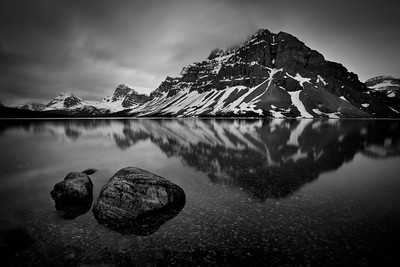 """""""Midnight at Bow Lake""""  Taken on the very still night of June 20th. The lake finished thawing a couple of days before meaning that all the major lakes along the Icefields Parkway were now ice-free.  I rarely go to B&W for night photographs but I liked the feel it gave this one and how it emphasized the composition.  Bow Lake and I have a long history and the traditional, meditative night stroll along the shore is always special."""