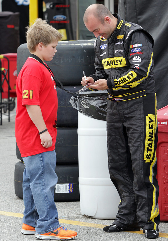 . DAYTONA BEACH, FL - FEBRUARY 20:  Marcos Ambrose, driver of the #9 Stanley Ford, signs an autograph in the garage area during practice for the NASCAR Sprint Cup Series Daytona 500 at Daytona International Speedway on February 20, 2013 in Daytona Beach, Florida.  (Photo by Jerry Markland/Getty Images)
