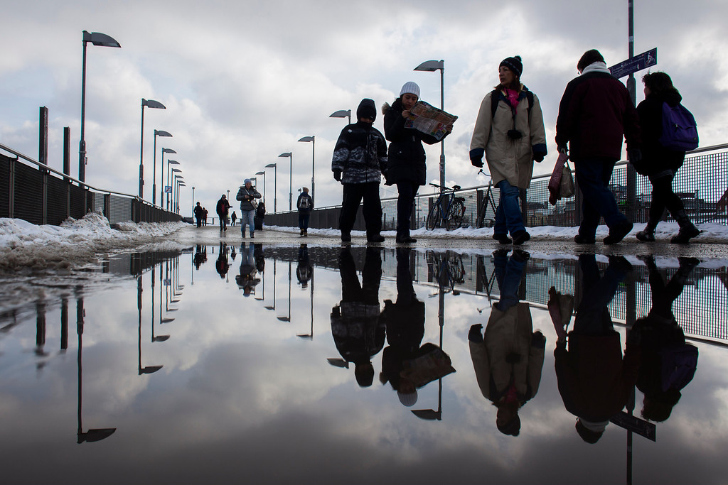 . Pedestrians reflected in a puddle  as they walk  across  a bridge of a public transport station at the district Friedrichshain  in Berlin, Tuesday, March 12, 2013.  (AP Photo/Markus Schreiber)