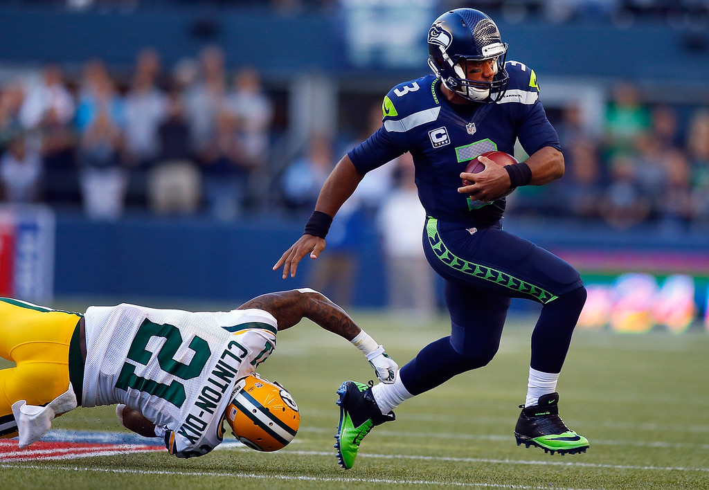 . SEATTLE, WA - SEPTEMBER 04: Quaterback Russell Wilson #3 of the Seattle Seahawks escapes the tackle attempt of safety Ha Ha Clinton-Dix #21 of the Green Bay Packers in the first quarter of the game at CenturyLink Field on September 4, 2014 in Seattle, Washington.  (Photo by Jonathan Ferrey/Getty Images)