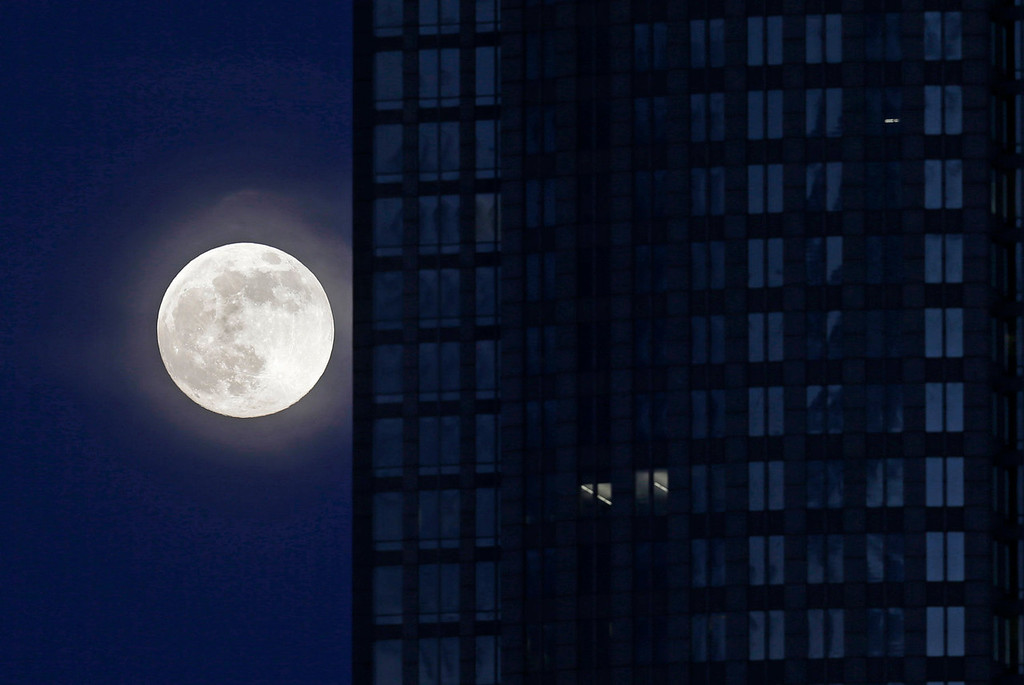 ". A full moon rises beside an office building in downtown Charlotte, N.C. on Saturday, June 22, 2013. The larger than normal moon called a ""super moon\"" happens only once this year as the moon on its elliptical orbit is at its closest point to Earth.  (AP Photo/Chuck Burton)"