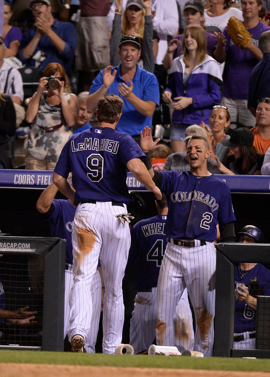 . Colorado Rockies shortstop Troy Tulowitzki (2) high fives Colorado Rockies DJ LeMahieu (9) after scoring on a Colorado Rockies center fielder Drew Stubbs (13) single against the Arizona Diamondbacks June 4, 2014 at Coors Field. (Photo by John Leyba/The Denver Post)