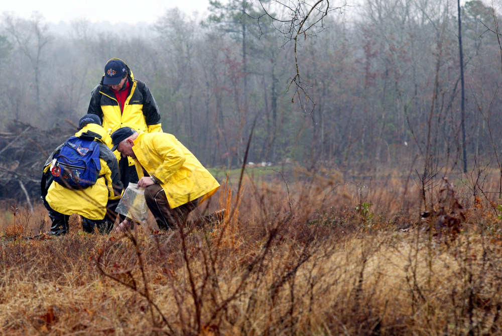 . A group of volunteers look closely at a piece of possible debris from the space shuttle Columbia Sunday, Feb. 9, 2003, near Nacogdoches, Texas. (AP Photo/The Dallas Morning News, Richard Michael Pruitt)