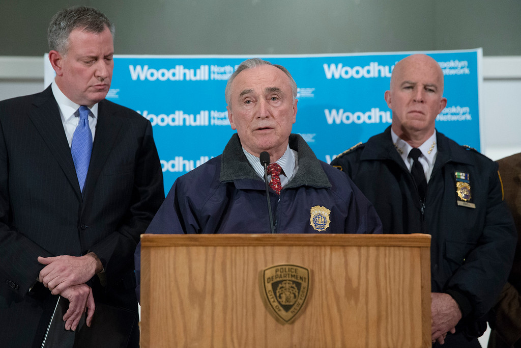 . New York Police Department Commissioner Bill Bratton speaks alongside Mayor Bill de Blasio, left, and NYPD\'s Chief of Department James O\'Neill, right, during a news conference at Woodhull Medical Center, Saturday, Dec. 20, 2014, in New York.  An armed man walked up to two New York Police Department officers sitting inside a patrol car and opened fire Saturday afternoon, killing one and critically wounding a second before running into a nearby subway station and committing suicide, police said. (AP Photo/John Minchillo)