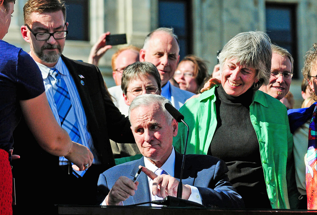 . Gov. Mark Dayton, center, is handed another pen as he signs the same-sex marriage bill on the steps of the state Capitol.Behind Dayton are state Sen. Scott Dibble, DFL-Minneapolis, and Rep. Karen Clark, DFL-Minneapolis, both of whom sponsored the bill. (Pioneer Press: Ben Garvin)