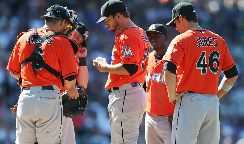 . Miami Marlins starting pitcher Brad Hand, center, waits to be pulled from the mound after yielding a bases-loaded walk to drive in a run to Colorado Rockies\' Michael McKenry in the fifth inning of the Rockies\' 7-4 victory in a baseball game in Denver on Sunday, Aug. 24, 2014. Looking on are, from left front, catcher Jeff Mathias, third baseman Casey McGehee, shortstop Adeiny Hechavarria and first baseman Garrett Jones. (AP Photo/David Zalubowski)