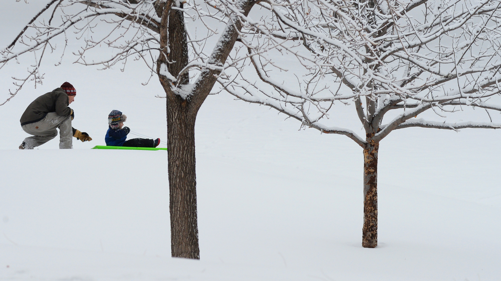 . Brian Brandy and his son Henry, 5, go sledding at Jefferson Park in Denver after a few inches of snow fell overnight, January, 31 2014. A smaller storm will move back into the area later today. (Photo by RJ Sangosti/The Denver Post)