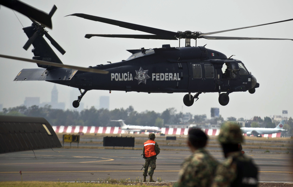 """. Members of the Mexican Navy stand guard next to a helicopter transporting Mexican drug trafficker Joaquin Guzman Loera aka \""""el Chapo Guzman\"""", on February 22, 2014 in Mexico City. The Sinaloa cartel leader - the most wanted by US and Mexican anti-drug agencies - was arrested early this morning by Mexican marines at a resort in Mazatlan, northern Mexico. (RONALDO SCHEMIDT/AFP/Getty Images)"""