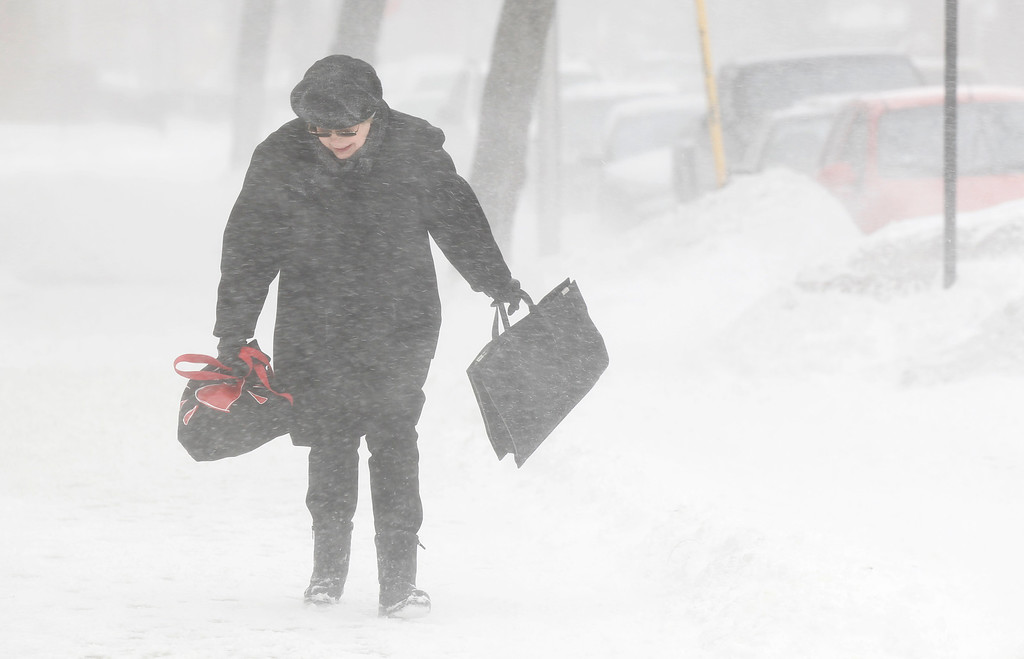 . A commuter walks against blowing snow Wednesday, Feb. 5, 2014, in Chicago. Heavy, blowing snow is moving across much of Illinois as the state gets pelted by the latest round of winter weather. (AP Photo/Kiichiro Sato)
