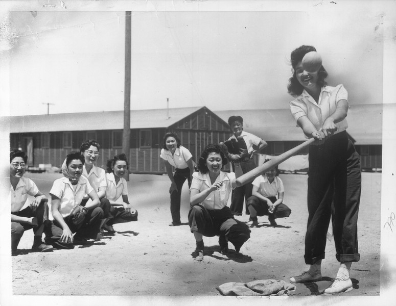 """""""How life goes between work hours for Japanese evacuates now living at the Manzanar relocation center [...] Maye Noma crouches behind the plate as Tomi Nagao goes to bat"""" -- caption on photograph"""