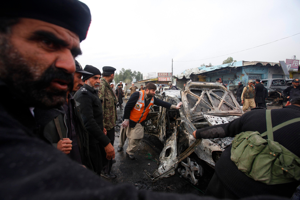 . Police officers try to move a car, which was damaged during a bomb attack at Fauji Market in Peshawar December 17, 2012. The blast in the market in northwest Pakistan on Monday killed at least 15 people, a security official said. The official said at least 20 people had been wounded in the blast in the market in the Khyber region, near the border with Afghanistan, and the death toll could rise.  REUTERS/Fayaz Aziz