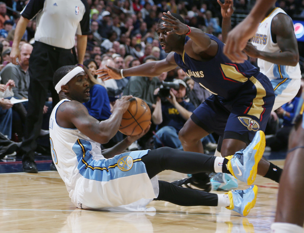 . Denver Nuggets guard Ty Lawson, left, looks to pass the ball as he falls to the floor while New Orleans Pelicans guard Jrue Holiday covers in the first quarter of an NBA basketball game in Denver on Sunday, Dec. 15, 2013. (AP Photo/David Zalubowski)