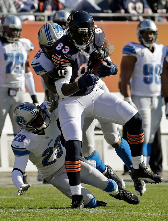 . Detroit Lions olinebacker DeAndre Levy (54) and cornerback Chris Houston (23) try to tackle Chicago Bears tight end Martellus Bennett (83) during the first half of an NFL football game, Sunday, Nov. 10, 2013, in Chicago. (AP Photo/Nam Y. Huh)