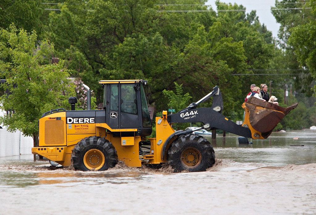 . A front end loader carries residents after they were rescued from the flood waters in High River, Alberta on Thursday, June 20, 2013 after the Highwood River overflowed its banks. Calgary city officials say as many as 100,000 people could be forced from their homes due to heavy flooding in western Canada, while mudslides have forced the closure of the Trans-Canada Highway around the mountain resort towns of Banff and Canmore. (AP Photo/The Canadian Press, Jordan Verlage)